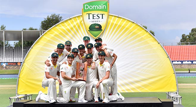 Australian players pose with the winning trophy after defeating Sri Lanka's in the second Test cricket match between Australia and Sri Lanka at the Manuka Oval Cricket Ground in Canberra on February 4, 2019. (Photo by Saeed KHAN / AFP) / -- IMAGE RESTRICTED TO EDITORIAL USE - STRICTLY NO COMMERCIAL USE --