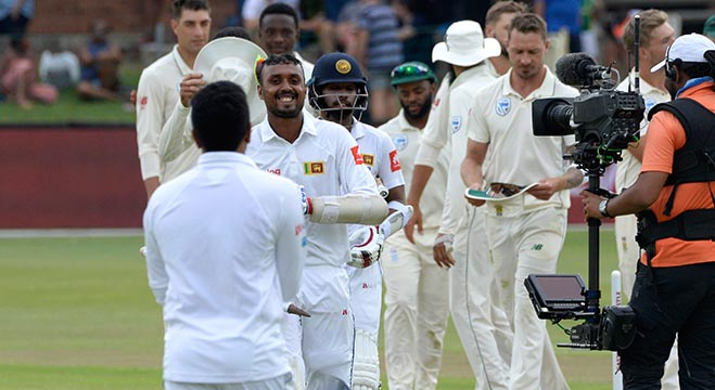 Sri Lanka's Oshada Fernando (2nd L) walks back to the pavilion after victory in the second Test cricket match between South Africa and Sri Lanka at St. George's Park Stadium in Port Elizabeth on February 23, 2019. (Photo by RODGER BOSCH / AFP)