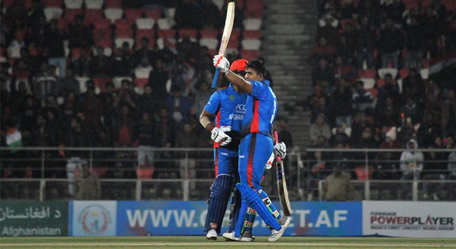 Afghan batsman Hazratullah Zazai raises his bat to celebrate a record breaking scoring run during Afghanistan's International Twenty20 (T20) cricket match against Ireland in the northern Indian city of Dehradun on February 23, 2019. - Hazratullah Zazai smashed the ball to every corner of the ground, and even out of the stadium, as Afghanistan racked up a world record T20 score of 278-3 in a crushing demolition of Ireland on February 23. (Photo by STR / AFP)