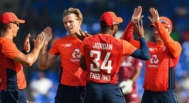 David Willey (2L), Chris Jordan (2R) and Eoin Morgan (R) of England celebrate the dismissal of Shimron Hetmyer of West Indies during the 3rd and final T20I between West Indies and England at Warner Park, Basseterre, Saint Kitts and Nevis, on March 10, 2019. (Photo by Randy Brooks / AFP)