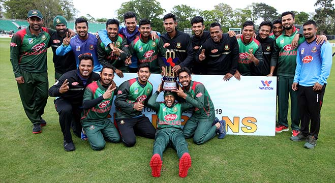 Bangladesh's Mushfiqur Rahim (C) holds the winner's trophy as Bangladesh cricketers celebrate victory after the one-day international Tri-Nation Series final between Bangladesh and West Indies at the Malahide cricket club, in Dublin on May 17, 2019. (Photo by Paul Faith / AFP)